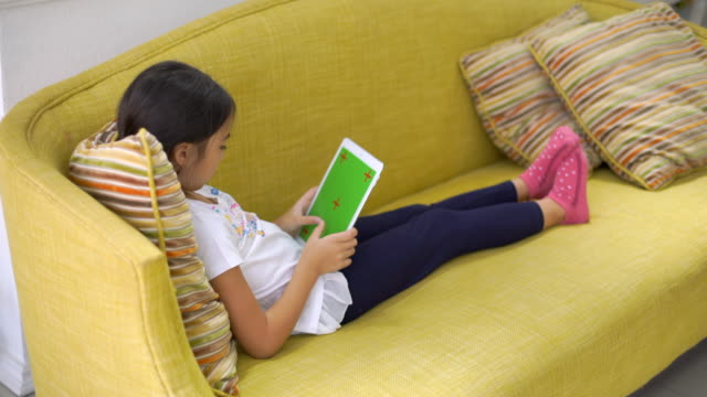 girl use digital tablet on sofa - one girl only stock videos & royalty-free footage