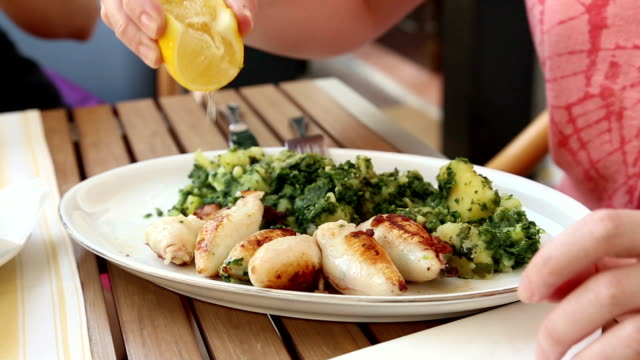 Girl use lemon for grilled squid