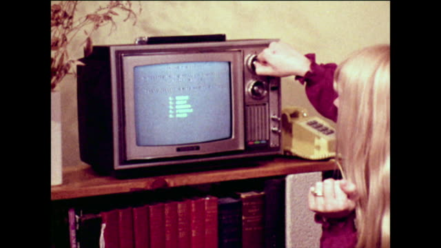 vídeos de stock e filmes b-roll de girl uses phone to select games on cable tv; 1973 - fora de moda estilo