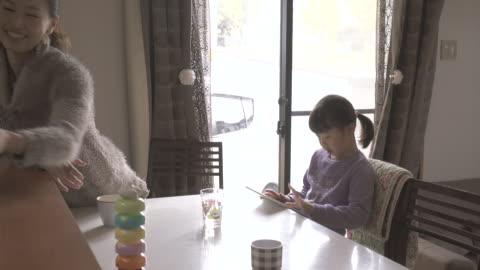 vídeos y material grabado en eventos de stock de girl using a digital tablet in the room - mesa de comedor