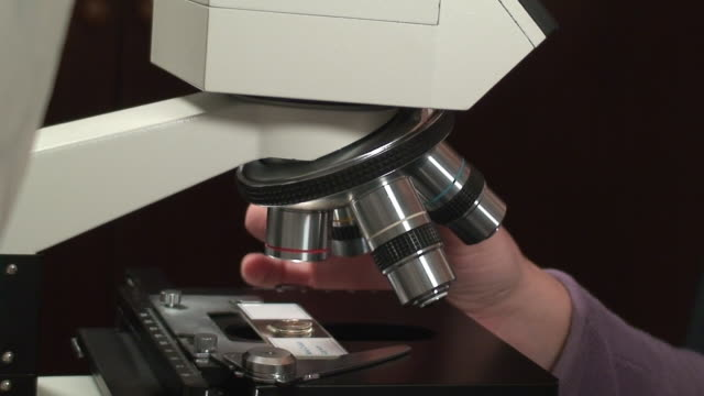stockvideo's en b-roll-footage met girl using a microscope - high scale magnification