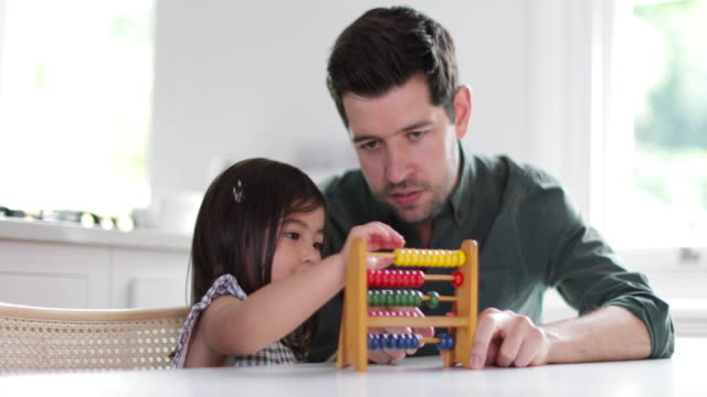girl using abacus to count with father - abakus bildbanksvideor och videomaterial från bakom kulisserna