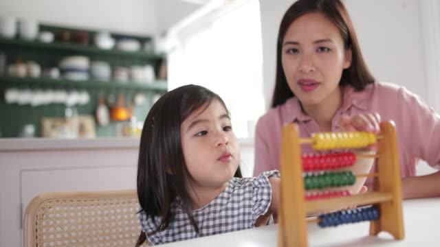 girl using abacus to count with mother - abakus bildbanksvideor och videomaterial från bakom kulisserna