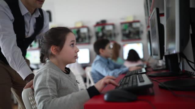vídeos y material grabado en eventos de stock de niña usando computadora durante la clase de computación con el profesor en la escuela privada - laboratorio de ordenadores