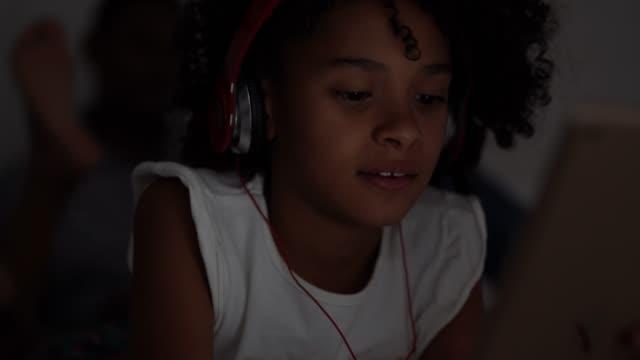 vídeos de stock, filmes e b-roll de menina que usa a tabuleta digital no quarto - brasileiro pardo