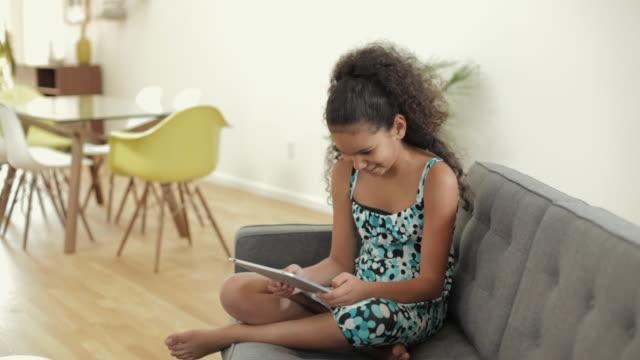 ms pan girl (10-11) using digital tablet sitting on sofa / vancouver, british columbia, canada - gambe incrociate video stock e b–roll