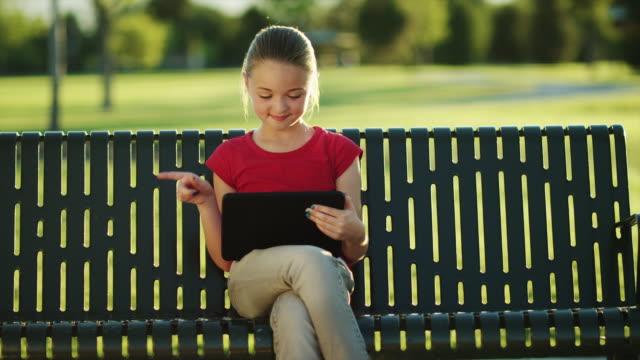 stockvideo's en b-roll-footage met ms girl (11-12) using digital tablet, sitting park bench / orem, utah, usa - orem utah