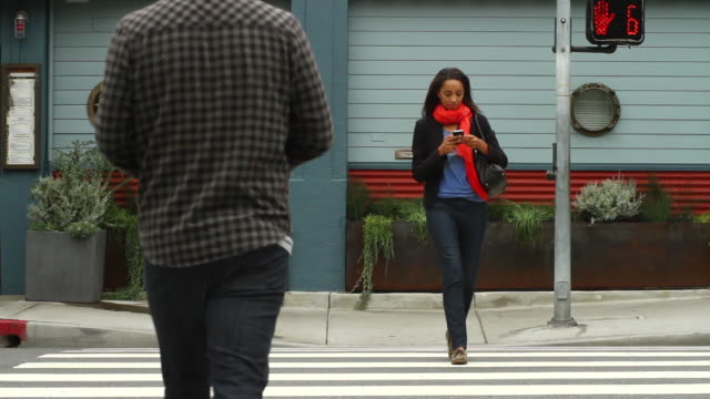 MS Girl using iPhone crossing street / Santa Monica, California, United States