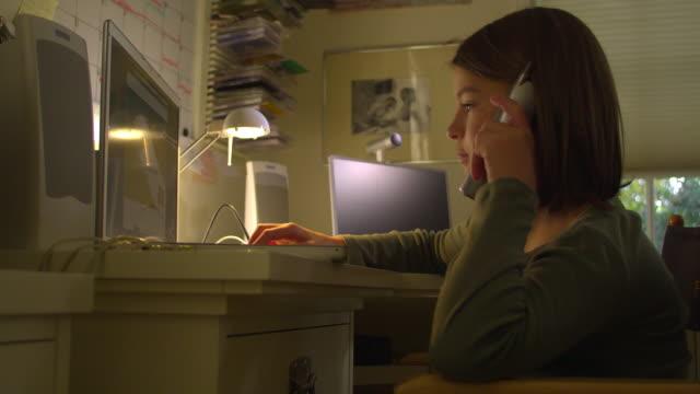 cu, pan, girl (10-11) using laptop and talking on phone at home, hollywood, california, usa - sladdlös telefon bildbanksvideor och videomaterial från bakom kulisserna