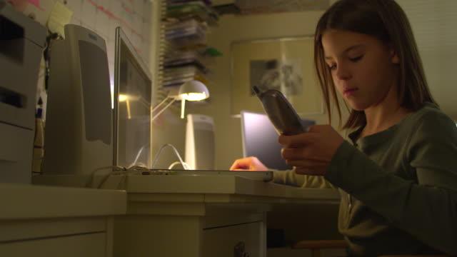 ms, pan, girl (10-11) using laptop and talking on phone at home, hollywood, california, usa - sladdlös telefon bildbanksvideor och videomaterial från bakom kulisserna