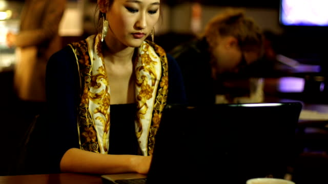girl using laptop in internet cafe / coffee shop - netbook stock videos and b-roll footage
