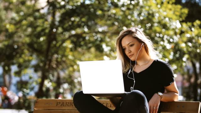 Girl using laptop in public park