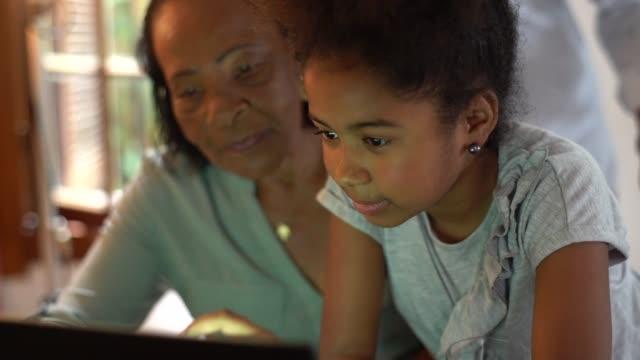 vídeos de stock, filmes e b-roll de menina usando laptop com avós - afro
