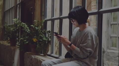 vidéos et rushes de jeune fille à l'aide de téléphone portable au bureau au domicile. - vue de dos