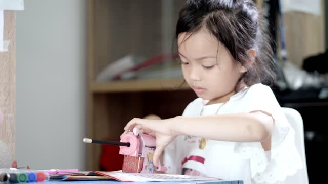 girl using pencil sharpener before doing homework at home, lifestyle concept. - pencil sharpener stock videos & royalty-free footage