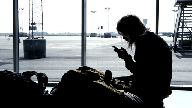 Girl using smart phone at airport terminal, waiting for flight