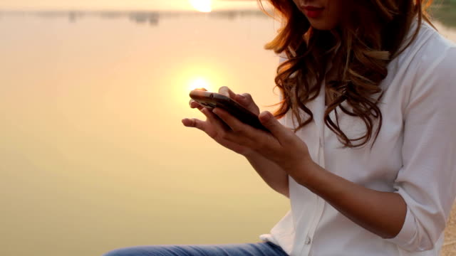 stockvideo's en b-roll-footage met girl using smart phone by the lake - elektronische organiser