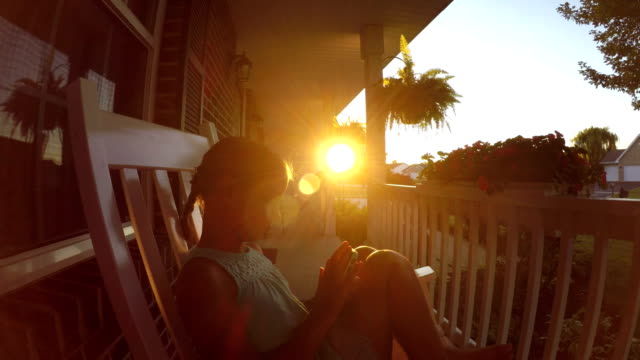 girl using smart phone on front porch of home - maglietta senza maniche video stock e b–roll