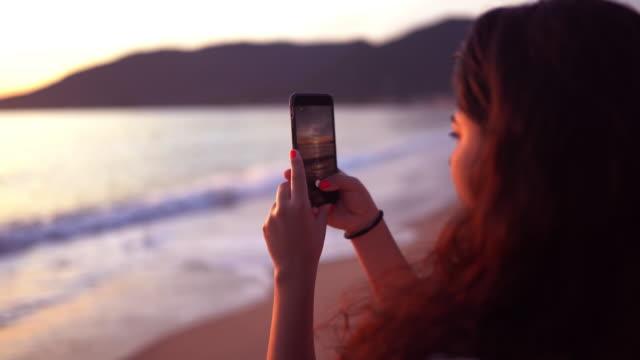 vídeos de stock, filmes e b-roll de menina que usa o smartphone em uma praia tropical - photographing