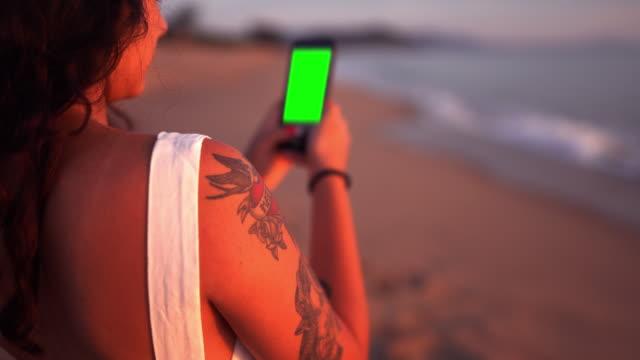 mädchen mit smartphone an einem tropischen strand - fotografieren stock-videos und b-roll-filmmaterial