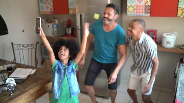 vídeos de stock, filmes e b-roll de menina usando smartphone para filmar família dançando em casa - imagem em movimento
