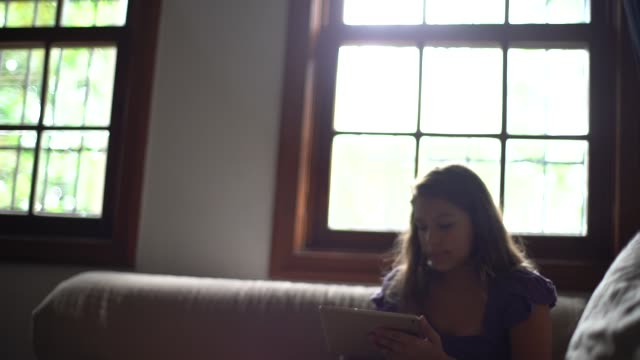 vídeos de stock, filmes e b-roll de menina usando tablet no sofá - brasileiro pardo