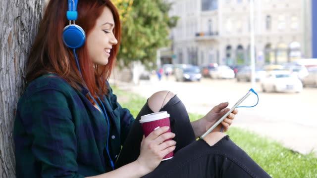 Girl using tablet pc and enjoying the music