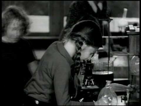 Girl w/ hair in pigtails looking into microscope in science class sharing look at slide w/ another girl
