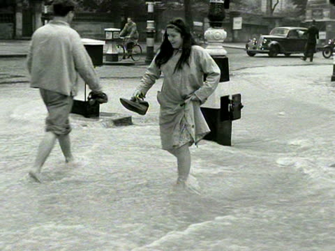 stockvideo's en b-roll-footage met a girl wades through flood waters on holland park avenue caused by a burst water main - blootvoets