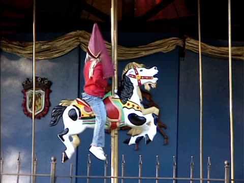girl waiting for parent on carrousel horse at festival - carousel horse stock videos and b-roll footage