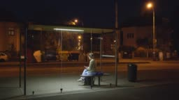 Girl waiting on bus stop shelter at night
