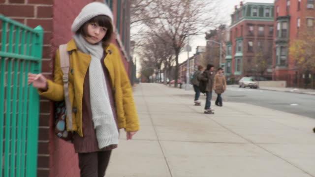 vídeos de stock e filmes b-roll de girl waiting outside school as boy skateboards - cachecol