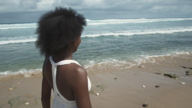 ms girl (14-15) walking along beach and in water, atlantic shores, bridgetown, barbados - walking in water stock videos & royalty-free footage