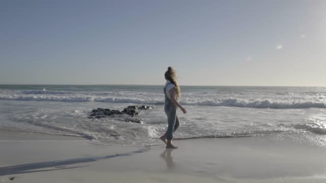 Girl walking at beach against sky on sunny day