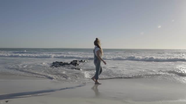 girl walking at beach against sky on sunny day - ein mädchen allein stock-videos und b-roll-filmmaterial