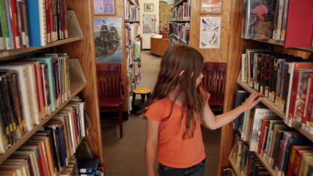 ms ts girl walking between bookshelves at library / flagstaff, arizona, usa - emotion stock videos & royalty-free footage