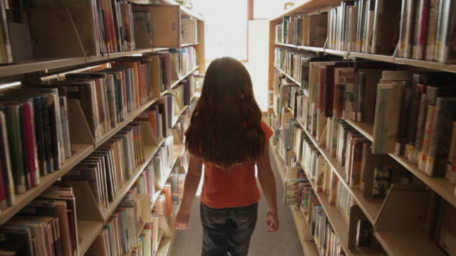ms ts girl walking between bookshelves at library / flagstaff, arizona, usa - bibliothek stock-videos und b-roll-filmmaterial