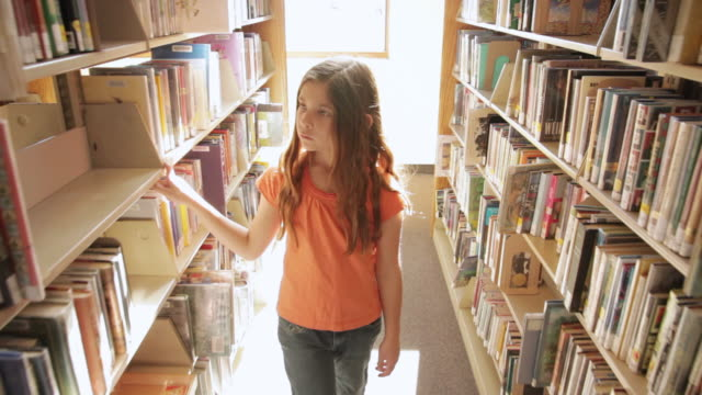 MS TS Girl walking between bookshelves at library / Flagstaff, Arizona, USA