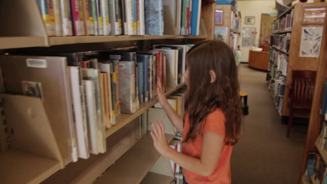 ms ts girl walking between bookshelves at library / flagstaff, arizona, usa - literature stock videos & royalty-free footage