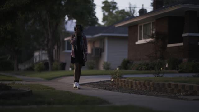 girl walking in neighborhood listening to music on headphones / provo, utah, united states - provo stock videos & royalty-free footage