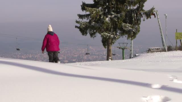 4K Girl walking in snow on sunny ski slope, slow motion