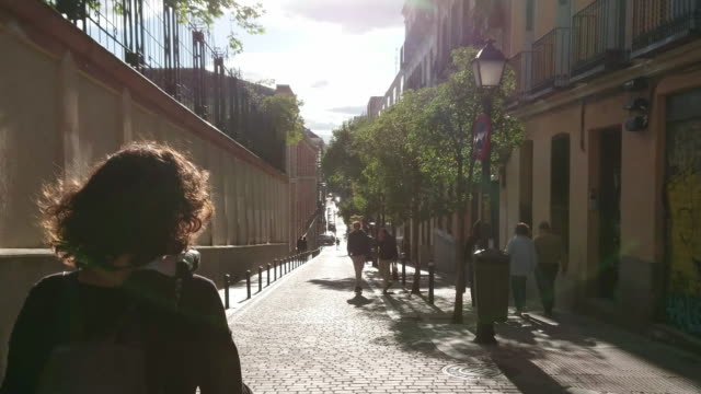 vídeos y material grabado en eventos de stock de chica caminando en las calles de malasaña de madrid al atardecer - zona residencial