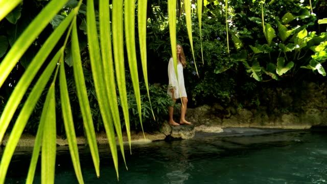 vidéos et rushes de fille marchant dans une piscine tropicale - robe blanche