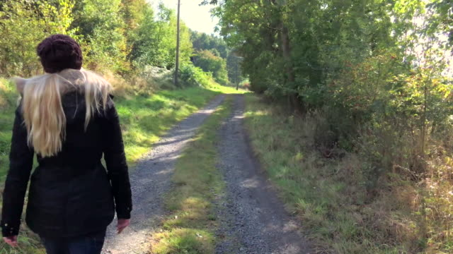 Girl walking on forest path