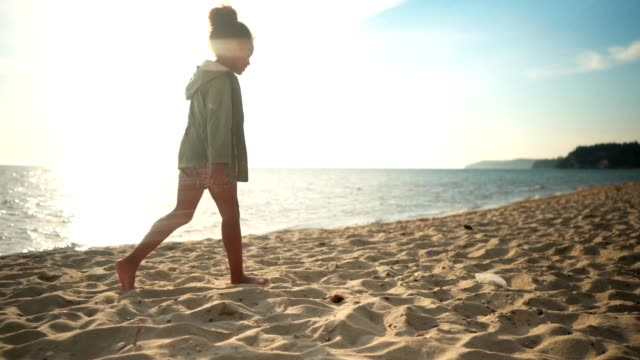Girl walking on sandy beach