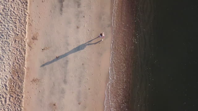 girl walking on the beach - track imprint stock videos and b-roll footage