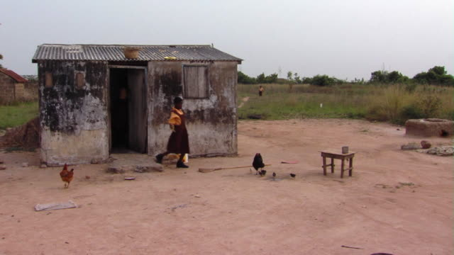 ms girl walking out of shack, washing table outdoors, tamale, ghana - ヒヨコ点の映像素材/bロール