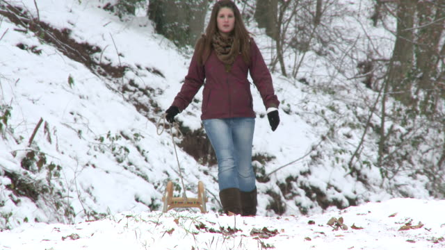 MS ZO  Girl walking through forest with sled  in winter / Saarburg, Rhineland-Palatinate, Germany