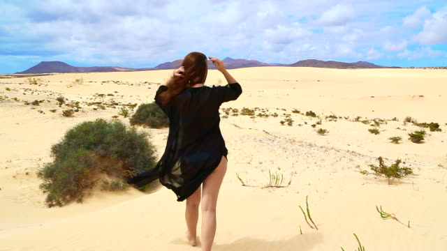 vídeos y material grabado en eventos de stock de girl walking with swimwear in the desert dunes of the fuerteventura island during travel vacations with nice breeze moving her dress with stunning landscape. - sarong