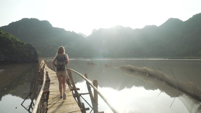 mädchen geht auf dock entlang bucht unter vietnamesischen bergen - rucksack stock-videos und b-roll-filmmaterial